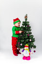 Baby boy dressed as santa s helper decorating christmas tree hanging ornaments white background Royalty Free Stock Photos