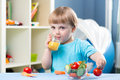 Baby boy drinking juice at table in children room Royalty Free Stock Photo