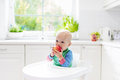 Baby boy eating apple in white kitchen at home Royalty Free Stock Photo