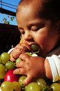 Baby boy eating grapes Royalty Free Stock Image