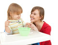 Baby boy eating with his young mother Royalty Free Stock Photo
