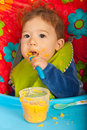 Baby boy eating puree vegetables by yourself and sitting in chair Royalty Free Stock Image