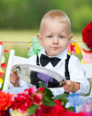 Baby boy at festive table sits holding silver tray Stock Images