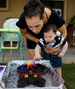 Baby boy first birthday party cute blowing away his candles from cat shaped cake Stock Photo