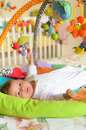 Baby boy with hanging toys is lying and watching Stock Photo