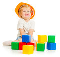 Baby boy in hard hat playing colorful building blocks with Royalty Free Stock Photography
