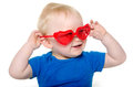 Baby boy with heart shaped sunglasses cute month old blond hair and blue shirt wearing on white background Royalty Free Stock Image