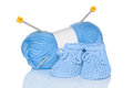 Baby boy knitted booties with blue wool and knitting needles isolated on a white background Stock Photos