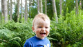 Baby boy laughing during walk in the woods Royalty Free Stock Image