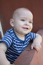 Baby boy leaning on railing by hotel. Bale baby. Royalty Free Stock Photo