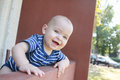Baby boy leaning on railing by hotel. Smiling baby boy. Royalty Free Stock Photo