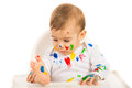 Baby boy looking at colorful paints on his body isolated on white background Royalty Free Stock Photo