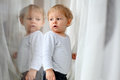 Baby boy looking at himself in reflection blond window Royalty Free Stock Images