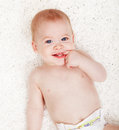 Baby boy with a mischievous look chewing on his finger Stock Photo