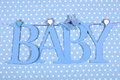 Baby boy nursery blue BABY letters bunting hanging from pegs on a line against a blue polka dot background Royalty Free Stock Photo