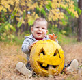 Baby boy outdoors with real pumpkin Royalty Free Stock Photos
