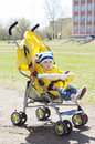 Baby boy outdoors on yellow buggy in spring carriage Stock Photos