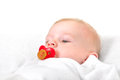 Baby boy with pacifier lying on the white blanket Royalty Free Stock Image