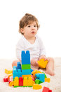 Baby boy playing with building blocks and sitting on fur carpet against white Stock Images