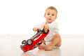 Baby boy playing with car toy big and sitting on floor in home Stock Photos