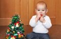 Baby boy playing with christmas tree Royalty Free Stock Image