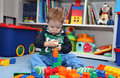 A baby boy playing with plastic blocks on the floor Royalty Free Stock Image