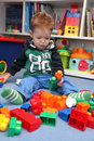 A baby boy playing with plastic blocks on the floor Royalty Free Stock Photo