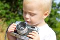 Baby boy playing with vintage camera a cute is sitting outside on a fall day a Stock Images