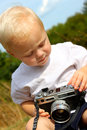 Baby boy playing with vintage camera a cute is sitting outside on a fall day a Royalty Free Stock Photography