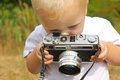 Baby boy playing with vintage camera a cute is sitting outside on a fall day a Stock Photos