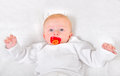 Baby boy portrait with pacifier on the white blanket Royalty Free Stock Photography