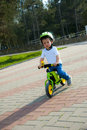 Baby boy riding on his first bike without pedals months old child learning to ride and balance two wheeler with Royalty Free Stock Photo