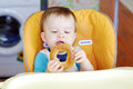 Baby boy with round cracknel age of year eating on kitchen Stock Photo