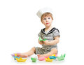 Baby boy with sailor hat playing with paper boats cute Stock Image