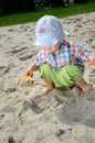 Baby boy in sandpit one and half year old playing wears simple hat shirt holds shovel and plays with the sand Stock Images