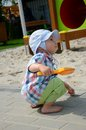 Baby boy in sandpit one and half year old playing wears simple hat shirt holds shovel and plays with the sand Stock Photography