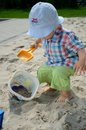 Baby boy in sandpit one and half year old playing wears simple hat shirt holds shovel and plays with the sand Royalty Free Stock Image