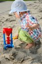 Baby boy in sandpit one and half year old playing wears simple hat shirt holds shovel and plays with the sand Stock Photo