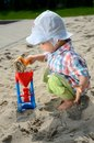 Baby boy in sandpit one and half year old playing wears simple hat shirt holds shovel and plays with the sand Royalty Free Stock Photos