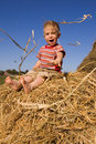 Baby boy sit on a hayrick Stock Photo