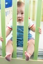 Baby boy is sitting in crib and looking through a safety fence Stock Photo