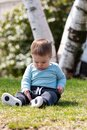 Baby boy sitting on grass in summer Royalty Free Stock Photo