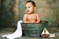Baby boy taking a bath in a tub green with toy boat Stock Images