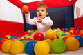 Baby boy throw the ball sitting in playpen with colorful balls and throwing a orange Royalty Free Stock Image