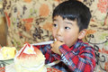 Baby boy to eat cream cake in a birthday party Stock Images