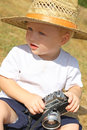 Baby boy with vintage camera a cute wearing a straw hat is sitting outside playing a Royalty Free Stock Photos