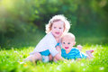 Baby brother and toddler sister in a garden cute little boy happy laughing girl playing together on green lawn the having Stock Photo