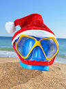 Baby bucket, diving mask and Santas hat on a beach Royalty Free Stock Photos