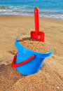 Baby bucket with sand and a shovel on the beach against the azure sea Royalty Free Stock Images