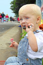 Baby with candy at parade a cute blonde boy is holding in his hands and watching people walk by in an american on a summer day Stock Photo